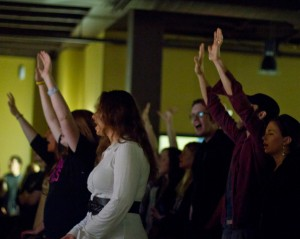 Worshipers singing and lifting hands at Sojourn Community Church's Midtown Campus. Photo taken by Chuck Heeke