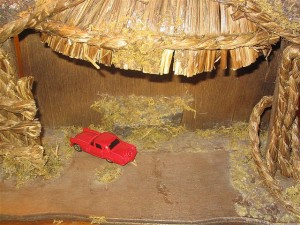Nativity Invasion: Red toy truck in a manger