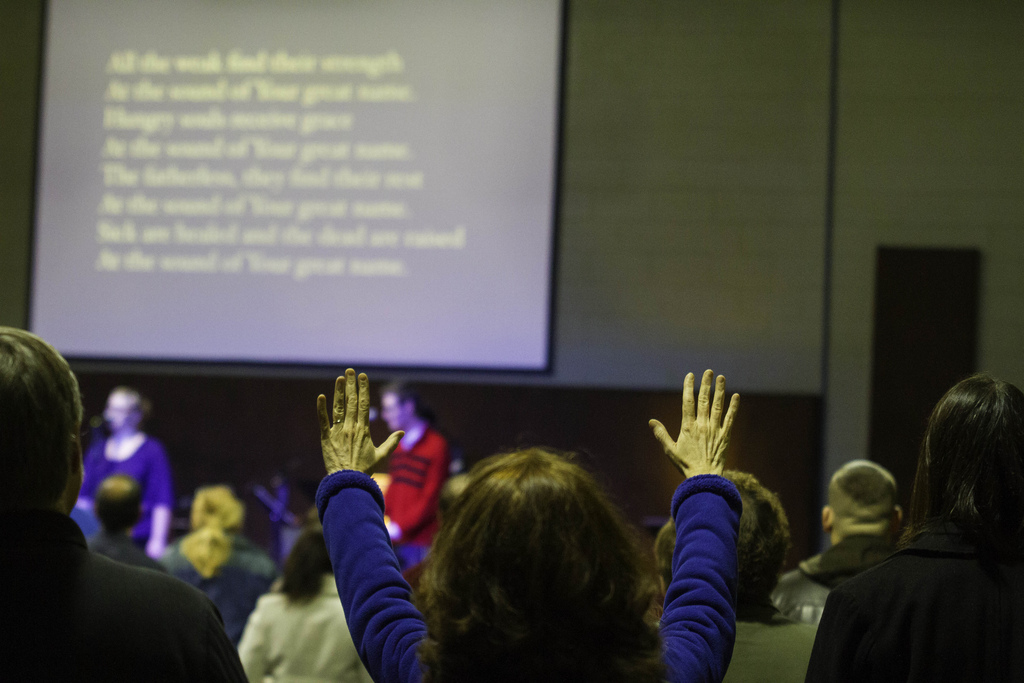 A worship with her hands in the air, in the midst of other worshipers at Sojourn New Albany Church.