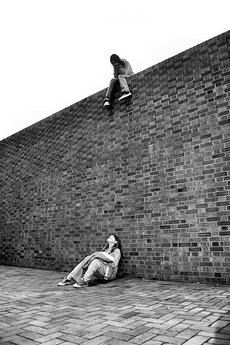 Two girls looking at each other - one sitting on top of high brick wall, one sitting on ground below