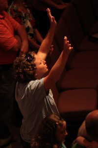 Woman raising hands in praise during Christian worship service at Sojourn Community Church