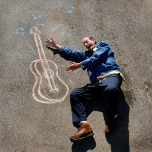 """Homeless man """"playing"""" image of a guitar written in chalk - part of Sojourn Church's """"In 3 Years"""" project (sojournvisualarts.com)"""