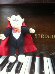 Stuffed vampire toy setting on the keys of a Stroud baby grand piano